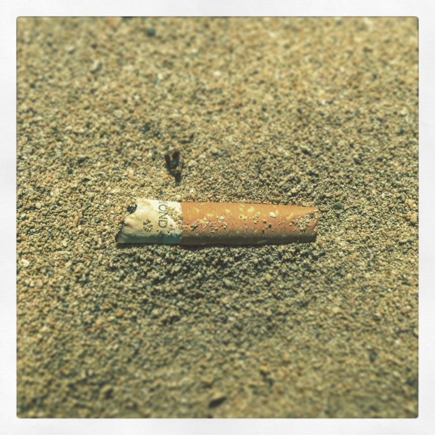 Zigarettenkippe am Sandstrand